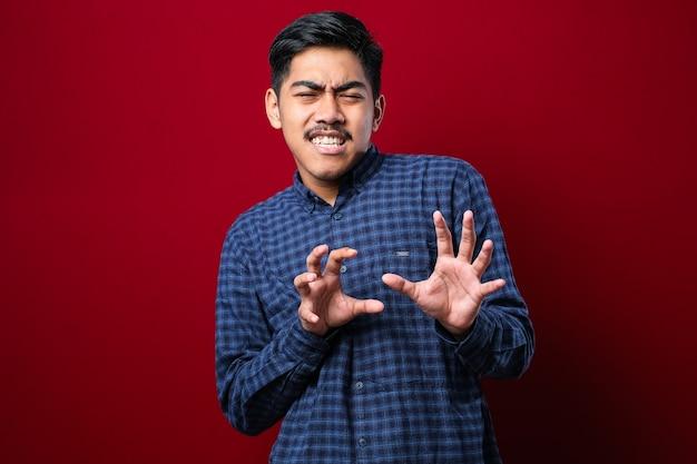Jonge knappe aziatische man met een casual shirt dat over een rode achtergrond staat bewegende handpalmen die weigering en ontkenning tonen met een bange en walgelijke uitdrukking. stop en verboden.