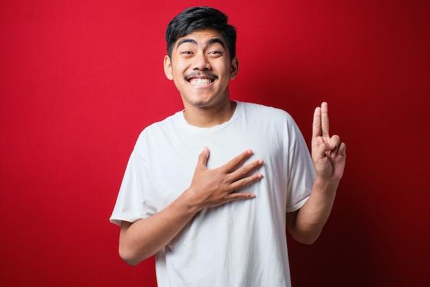 Jonge knappe aziatische man met een casual shirt over een rode achtergrond glimlachend vloekend met de hand op de borst en vingers omhoog, een loyaliteitsbelofte afleggend