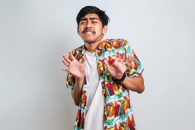 Jonge knappe aziatische man met een casual shirt over een witte achtergrond de handpalmen wegtrekken die weigering en ontkenning tonen met een bange en walgelijke uitdrukking. stop en verboden.