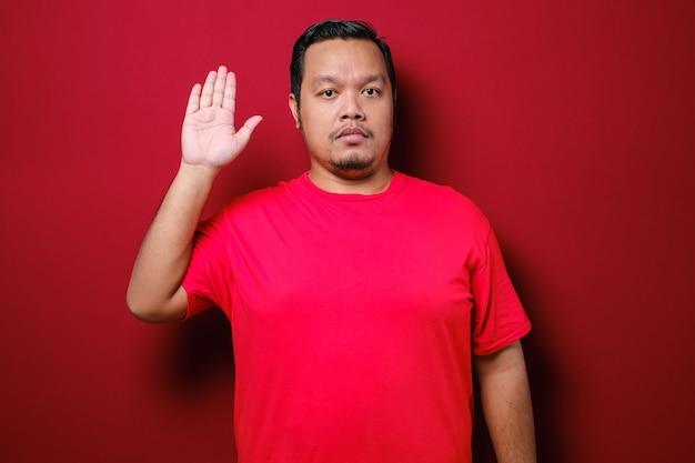 Jonge knappe aziatische man met een rood t-shirt die over een geïsoleerde rode achtergrond staat vloekend met de hand op de borst en open palm, een eed van loyaliteit afleggen