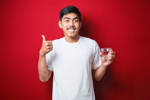 Jonge knappe aziatische man met een wit t-shirt die een glas water drinkt en duim omhoog wijst naar de zijkant glimlachend gelukkig met open mond over rode achtergrond