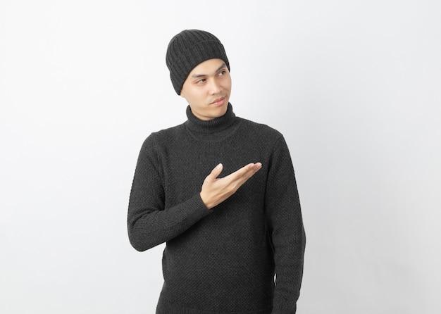 Jonge knappe aziatische man met grijze trui en muts wijzend naar de kant met handen om een product of een idee te presenteren