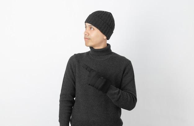 Jonge knappe aziatische man met grijze trui, handschoenen en muts wijzend naar de kant met handen om een product of een idee te presenteren