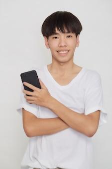 Jonge knappe aziatische man met mobiele telefoon op witte studio achtergrond
