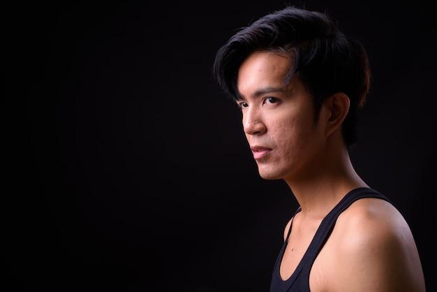 Jonge knappe aziatische man op zwart