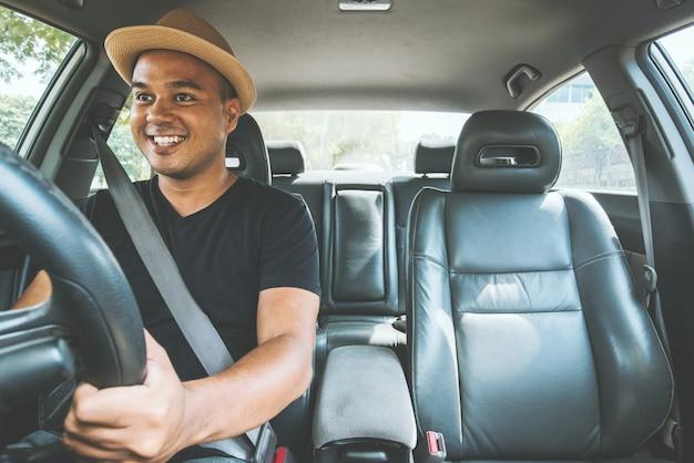 Jonge knappe aziatische man rijdende auto