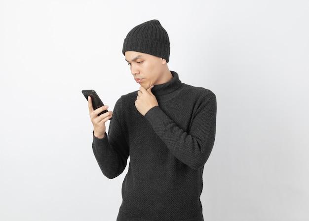 Jonge knappe aziatische mens die grijze sweater dragen en beanie terwijl het spelen van smartphone met twijfelsgezicht op wit