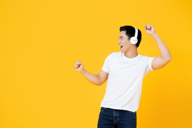 Jonge knappe aziatische mens die hoofdtelefoons draagt die aan muziek luistert en op gele muur danst