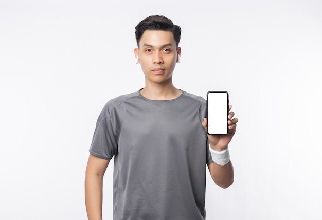 Jonge knappe aziatische mens in sportuitrustingen die telefoon met het lege scherm tonen