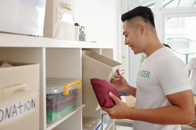 Jonge knappe aziatische vrijwilliger die op het kantoor van een liefdadigheidsstichting werkt, controleert de donatieboxen na het evenement