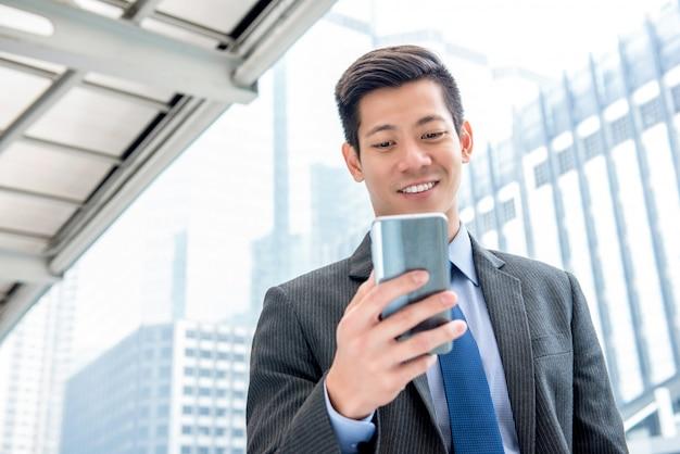 Jonge knappe aziatische zakenman die mobiele telefoon in openlucht met behulp van