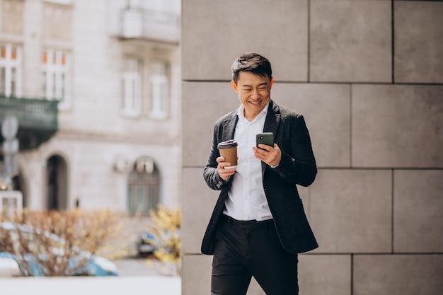 Jonge knappe aziatische zakenman in zwart pak met behulp van telefoon en koffie drinken