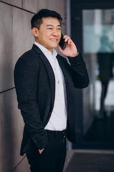 Jonge knappe aziatische zakenman in zwart pak met behulp van telefoon