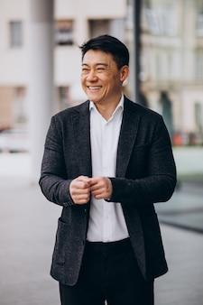Jonge knappe aziatische zakenman in zwart pak