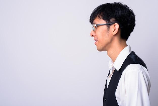 Jonge knappe aziatische zakenman tegen witte muur