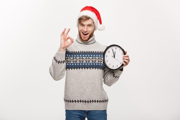 Jonge knappe baardmens in sweater met witte klok die ok teken geeft.