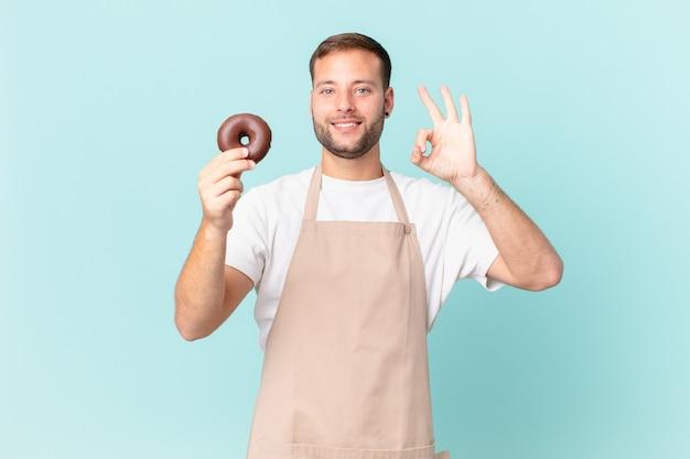 Jonge knappe bakker met een donut
