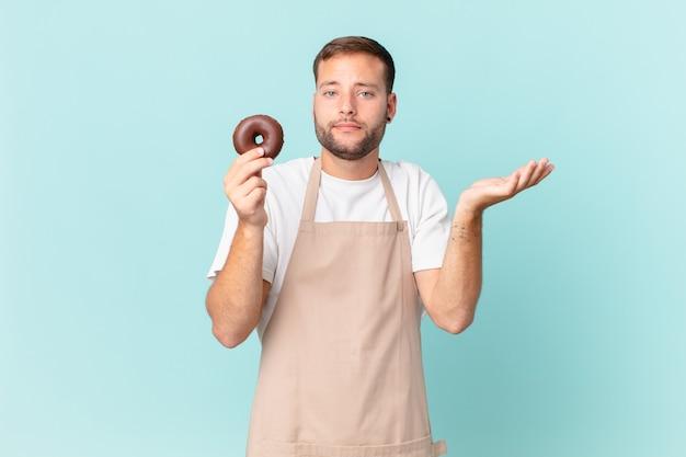 Jonge knappe bakker met een donut Premium Foto