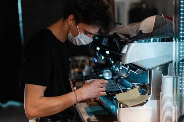 Jonge knappe barista-man met medisch beschermend masker die koffie maakt in de buurt van een koffiezetapparaat in café