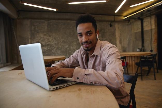 Jonge knappe bebaarde freelancer met donkere huid op afstand werken met moderne laptop in coworking space, handen op toetsenbord houden en vrolijk naar camera kijken