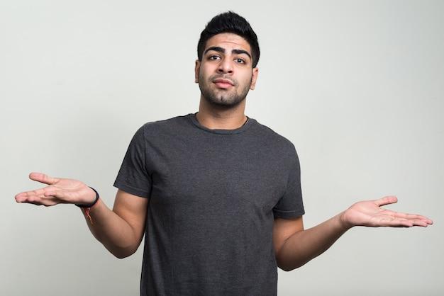 Jonge knappe bebaarde indiase man tegen witte muur
