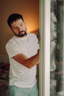 Jonge knappe bebaarde man doet voorjaarsschoonmaak in een gezellig appartement dat raam met doek wast