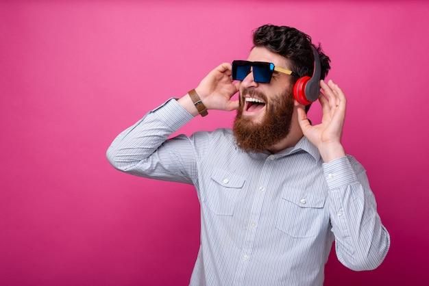 Jonge knappe bebaarde man luisteren naar de muziek op de koptelefoon, bril dragen poseren op roze achtergrond.