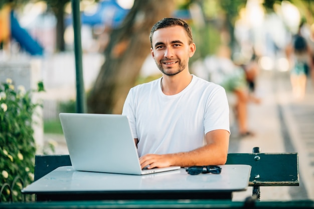 Jonge knappe bebaarde man met behulp van een laptop in een café op straat