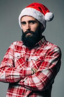 Jonge knappe bebaarde man met rode kerstmuts op grijze muur