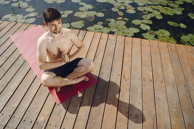 Jonge knappe bebaarde man zittend op houten pier in zomerdag. mediteren en ontspannen.