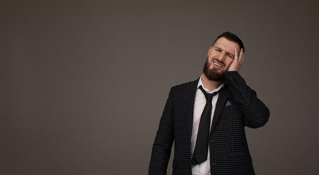 Jonge knappe bebaarde zakenman draagt pak over grijze achtergrond met hand op hoofdpijn omdat stress. lijdt aan migraine.