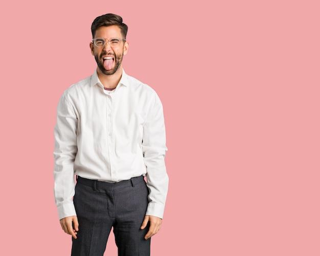 Jonge knappe bedrijfsman funnny en vriendschappelijke tonende tong