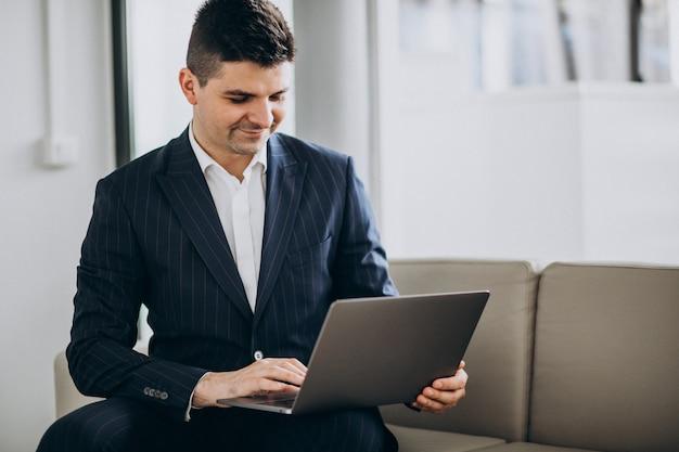 Jonge knappe bedrijfsmens die aan computer op een bank in bureau werkt