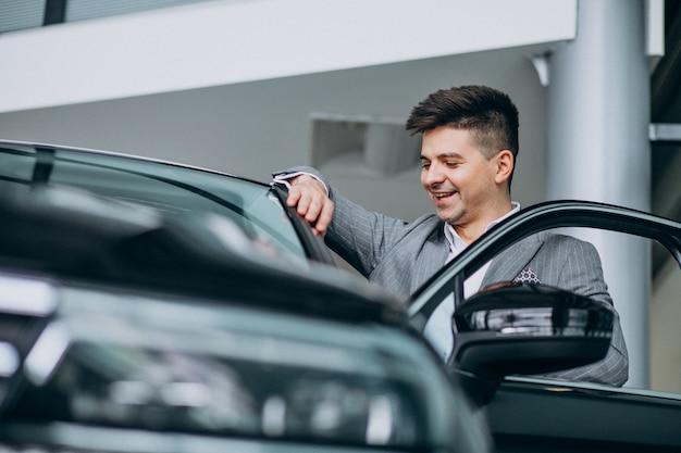 Jonge knappe bedrijfsmens die een auto in een autotoonzaal kiest