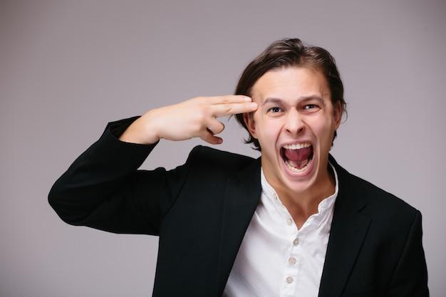 Jonge knappe bedrijfsmens die kostuum en stropdas over geïsoleerde muur draagt, schiet en doodt zichzelf wijzende hand en vingers als een pistool