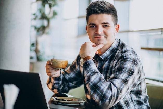 Jonge knappe bedrijfsmens die laptop in een koffie met behulp van