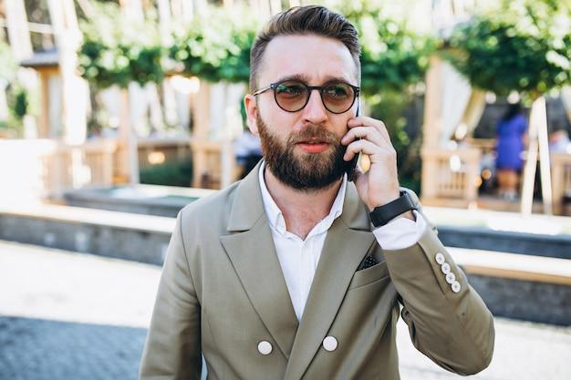 Jonge knappe bedrijfsmens die telefoon met behulp van