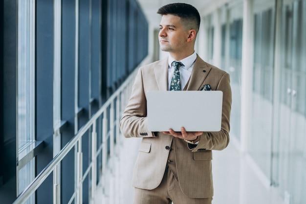Jonge knappe bedrijfsmens die zich met laptop op het kantoor bevindt