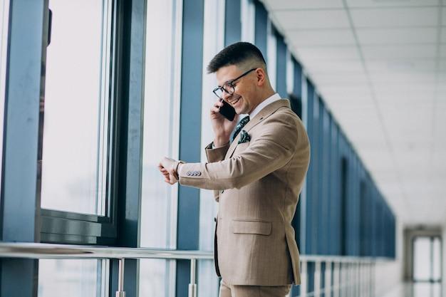Jonge knappe bedrijfsmens die zich met telefoon op het kantoor bevindt