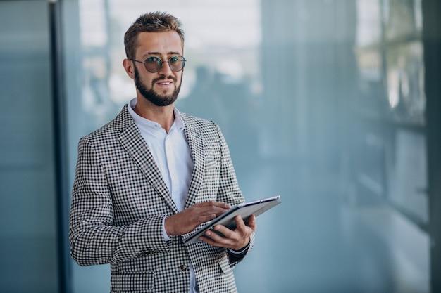 Jonge knappe bedrijfsmens in de tablet van de bureauholding