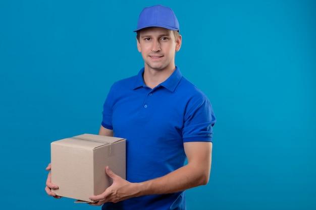 Jonge knappe bezorger in blauw uniform en glb bedrijf doos pakket glimlachend vriendelijk blij en positief staande over blauwe muur