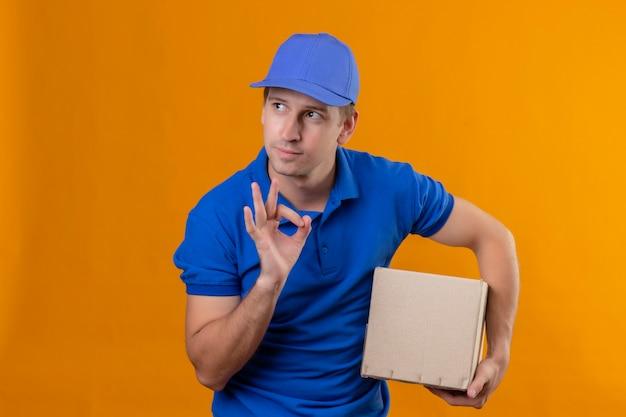 Jonge knappe bezorger in blauw uniform en glb bedrijf doos pakket opzij kijken