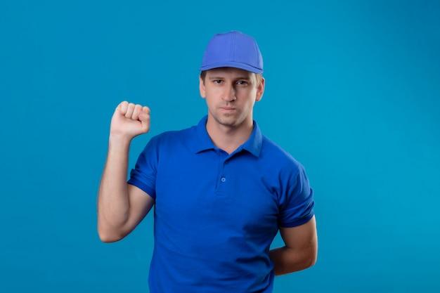 Jonge knappe bezorger in blauw uniform en pet die vuist opheft met een ernstige zelfverzekerde uitdrukking op gezicht dat zich over blauwe muur bevindt