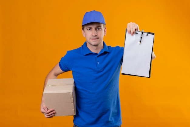 Jonge knappe bezorger in blauw uniform en pet met doos pakket en klembord met zelfverzekerde serieuze uitputting wachtend op handtekening staande over oranje muur