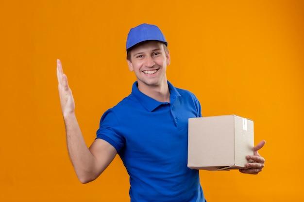 Jonge knappe bezorger in blauw uniform en pet met doos pakket glimlachend vriendelijk staande over oranje muur
