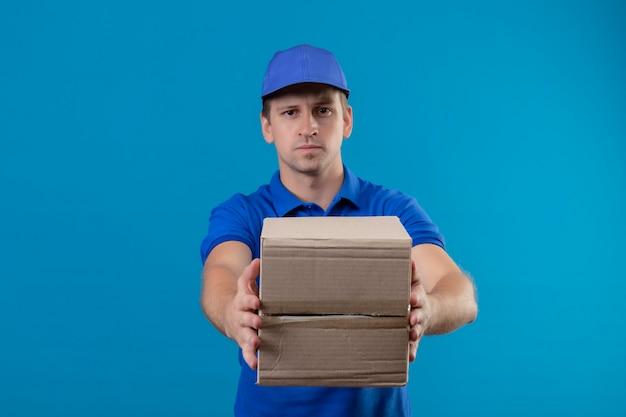 Jonge knappe bezorger in blauw uniform en pet met doos pakket strekt het uit naar de camera met een ernstige uitdrukking op het gezicht staande over de blauwe muur