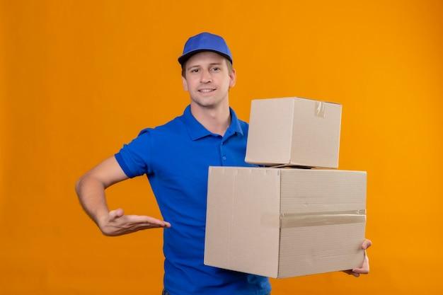 Jonge knappe bezorger in blauw uniform en pet met kartonnen dozen presenteren met armof zijn hand staande over oranje muur