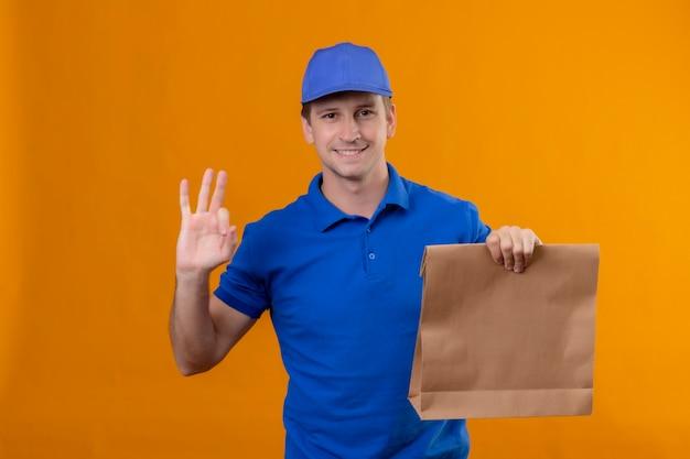 Jonge knappe bezorger in blauw uniform en pet met papieren pakket positief en gelukkig ok teken staande over oranje muur