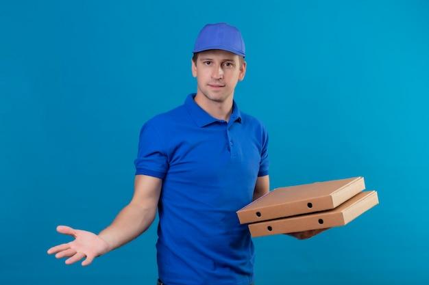 Jonge knappe bezorger in blauw uniform en pet met pizzadozen op zoek verward staand met opgeheven arm als het stellen van vraag over blauwe vackground