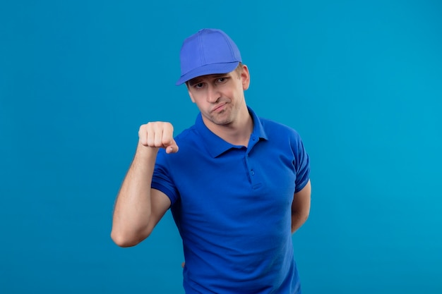 Jonge knappe bezorger in blauw uniform en pet met sceptische glimlach gebalde vuist als groetgebaar staande over blauwe muur